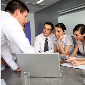 A group of 5 employees in business attire huddled around a laptop working