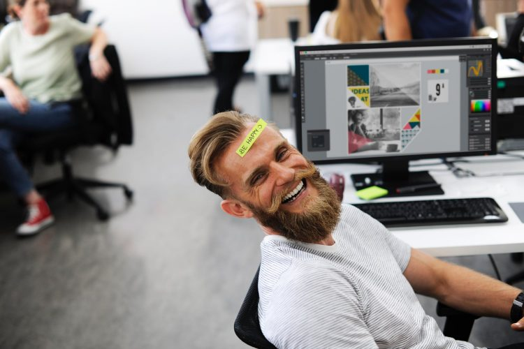 A graphic design employee at his desk with a post it note on his head that says