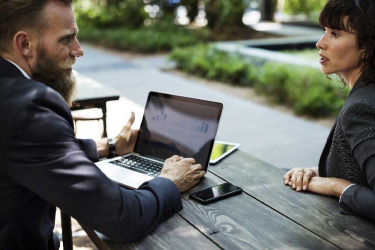 Two business people talking in a park about work with their laptop out | Career Coaching