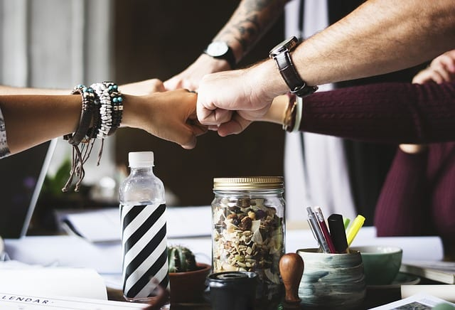 A group of employees fist bumping over office supplies, potpourri, and a water bottle | better benefits leads to better teams