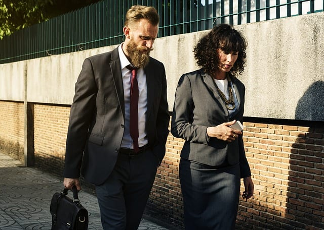 Two business people walking outside while carrying their things talking about sexual harassment in the workplace