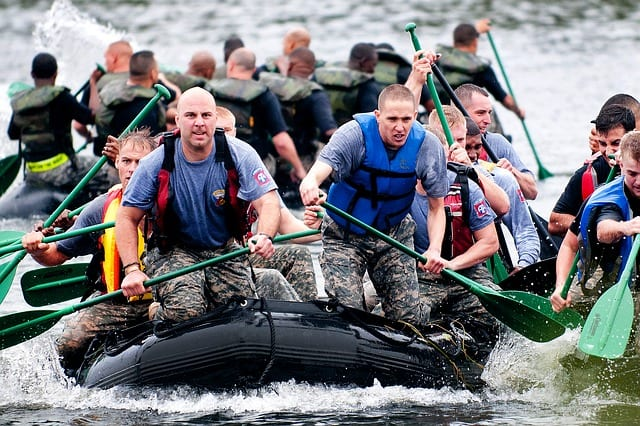 A large group of military personnel on rafts in shaky waters