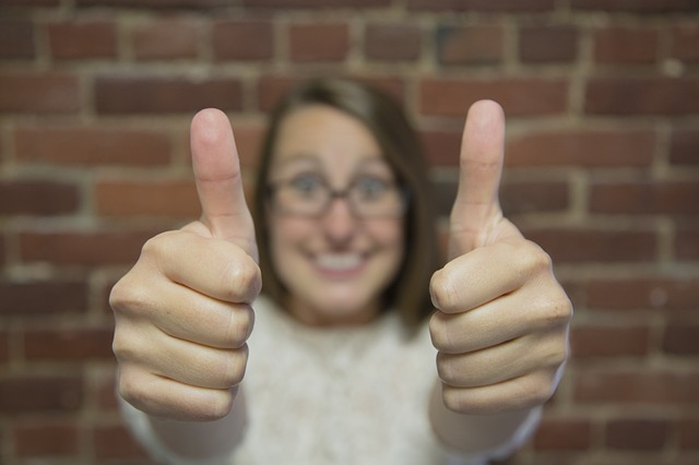 A woman giving two thumbs up in a modern day office | candidate retention