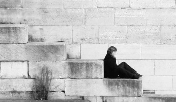 A woman sitting on steps thinking to herself outside