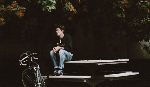 A young adult sitting at a park looking at a bike