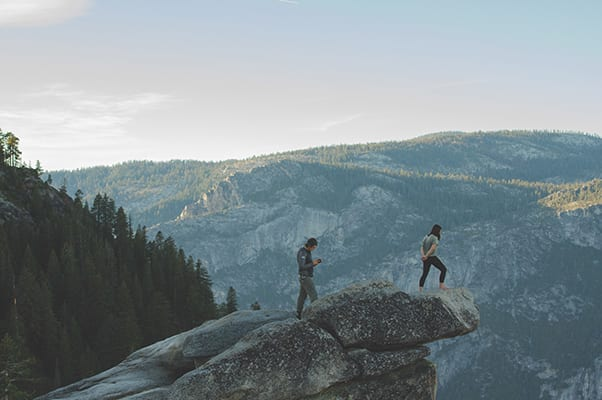 Two people hiking overlooking the mountains with trees in the background
