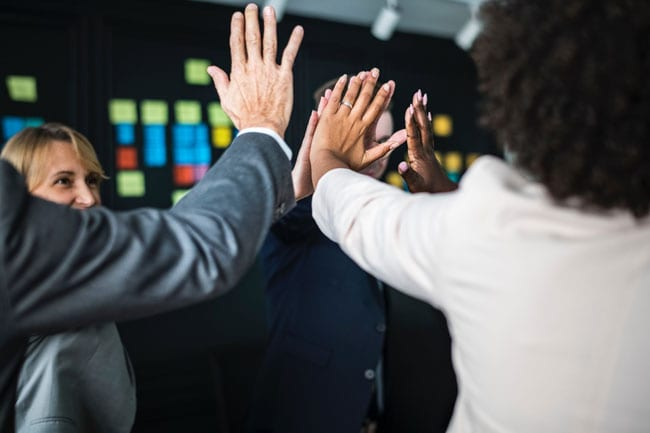 HR consultants high five in a conference room
