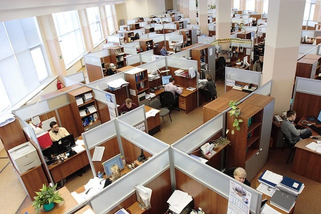 A modern day office filled with employees working at cubicles