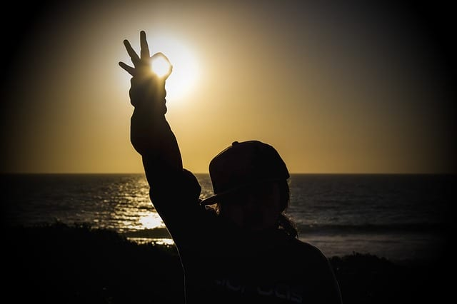 A person on a beach giving the OK symbol with the sun shining through | mental health in the workplace