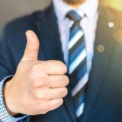 A business person in a suit giving a thumbs up