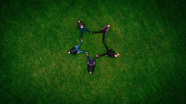 Five people sitting in the grass forming a star with their legs