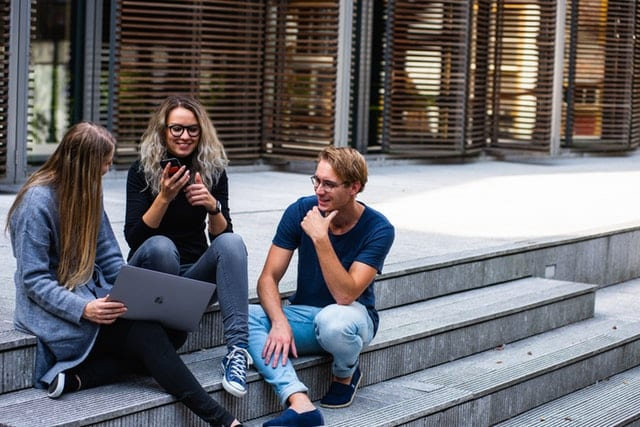3 young adults sitting on steps on their laptop and phone | Understanding HR Consulting Millennials