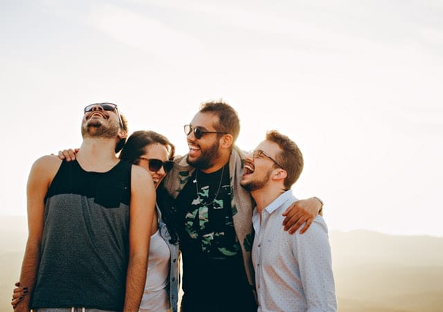 A group of young adults laughing and carrying on outdoors