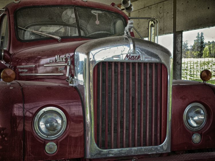 A maroon vintage Mack car in a garage with greenery in the background, union relations
