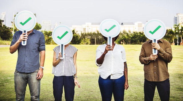 Four people holding checkmark signs with a park in the background