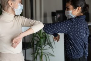 Employees elbow-bump after successful meeting during COVID pandemic