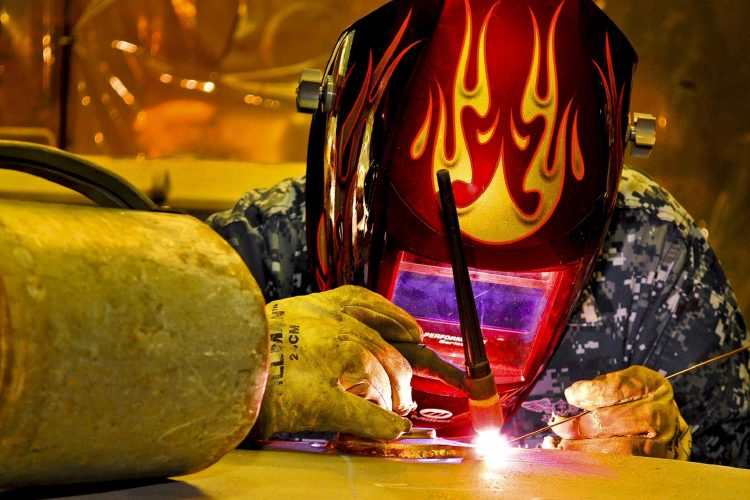 attracting craft labor | A fabricator working on a metal piece in protective gear