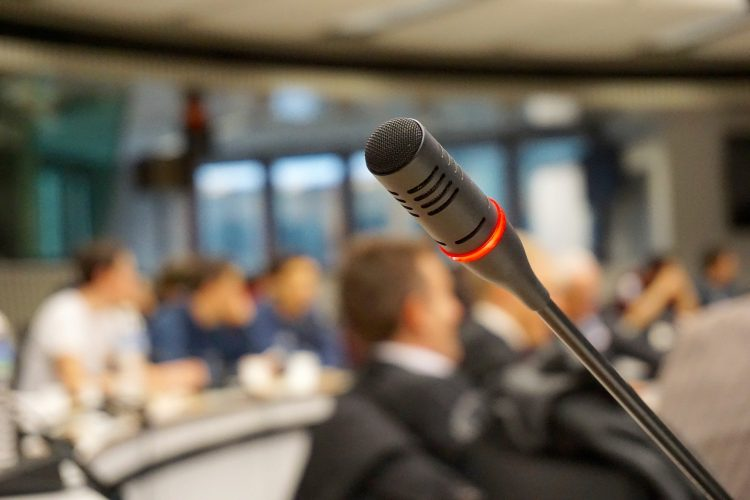 A microphone in a conference room filled with people| Is unconscious bias worth it?