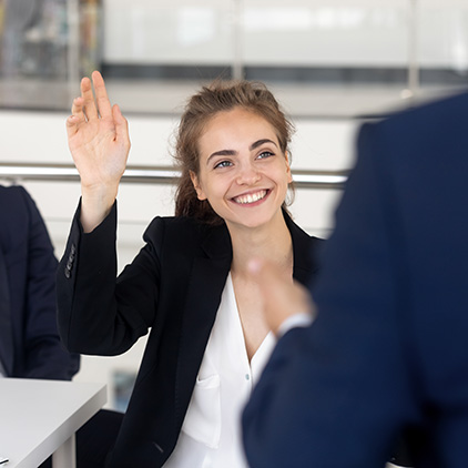 A female consultant raising her hand in a business meeting