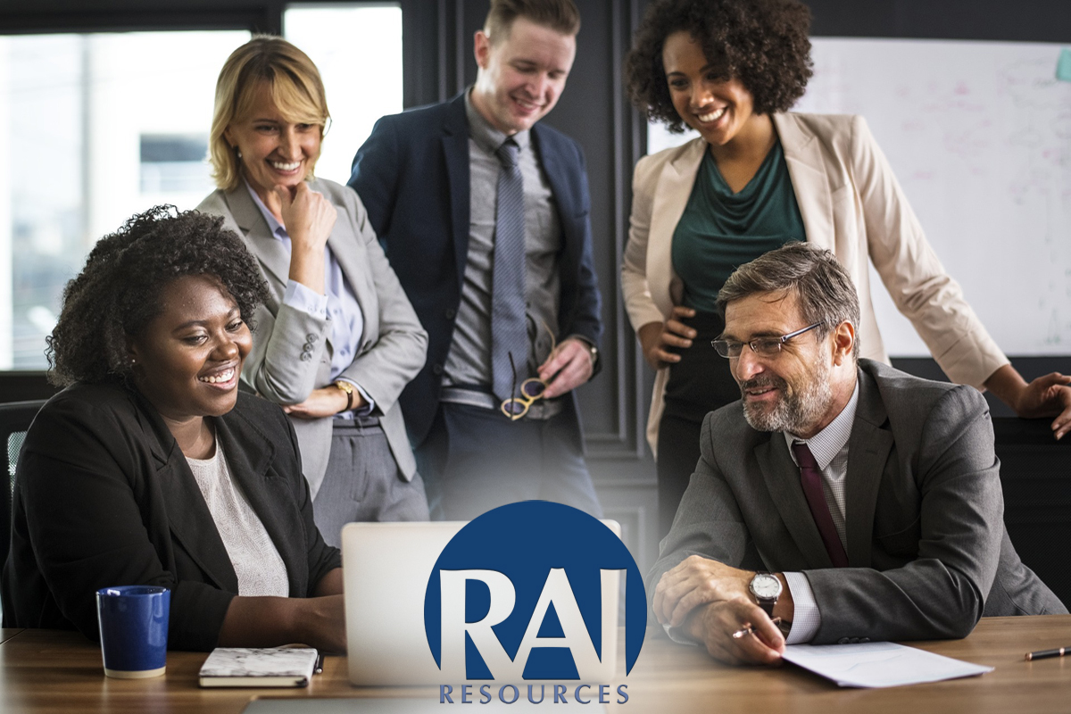 A group of 5 business people looking at a laptop in an office with the RAI Resources logo